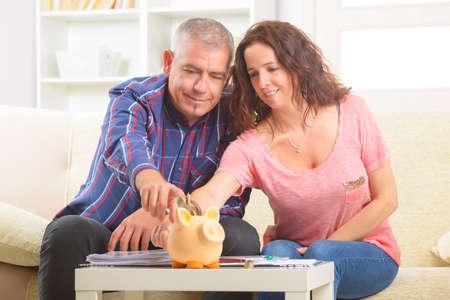 Happy couple putting money in piggybank, concept of saving Stock Photo - 27907215
