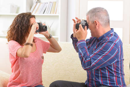 Mature couple at home taking pictures with old analog SLR cameras Stock Photo - 28830134