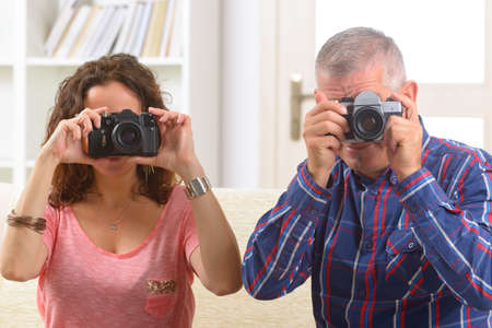 Mature couple at home taking pictures with old analog SLR cameras Stock Photo - 28830269