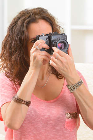 Mature woman taking pictures with old analog SLR camera at home Stock Photo - 28830271