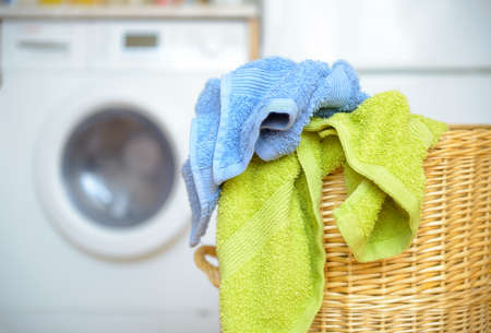 laundry: Dirty clothes basket with towels waiting for laundry with washing machine in backround Stock Photo