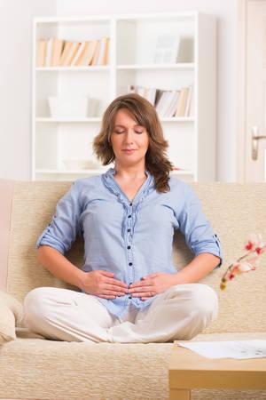 SELF HEALING: Woman practicing self Reiki transfering energy through palms, a kind of energy medicine  Stock Photo