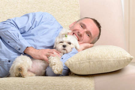 Little dog maltese with his owner on the sofa in home photo