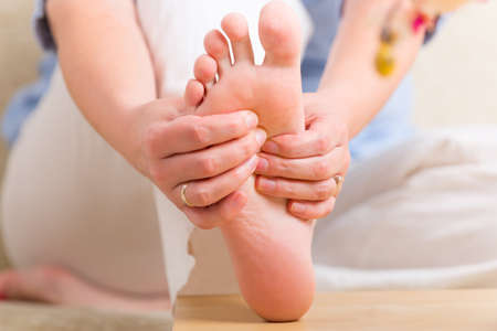 eastern health treatment: Hands doing feet reflexology or zone therapy at home