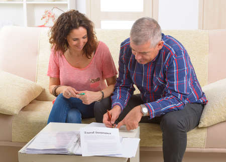 Couple signing travel insurance contract at home Stock Photo - 29391002