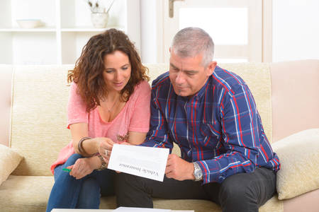 Couple signing vehicle insurance contract at home Stock Photo - 29391010