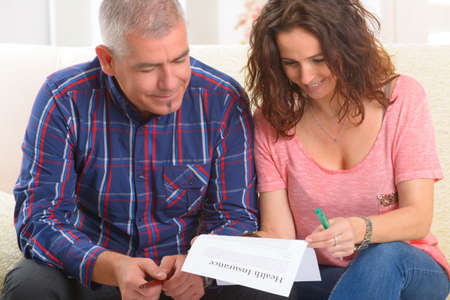 Mature ouple signing health insurance contract at home photo