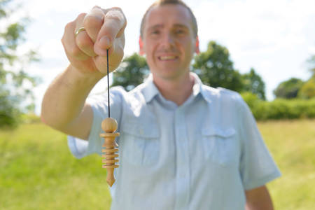 Man dowser using wooden pendulum, tool for dowsing  photo