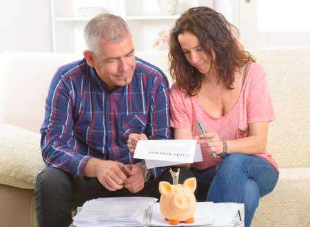 Couple signing credit insurance contract at home Stock Photo - 29467467