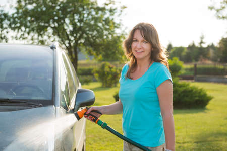 rinse spray hose: Woman washing her car in garden without detergents in ecological way