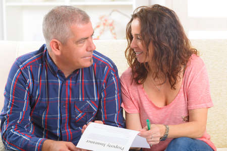 Couple signing property insurance contract at home photo