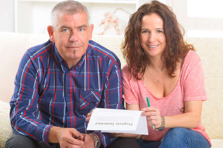 Couple signing property insurance contract at home Stock Photo - 29467473