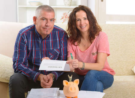 financial insurance: Couple signing life insurance contract at home