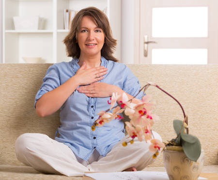 healing practitioners: Woman practicing self Reiki transfering energy through palms, a kind of energy medicine  Stock Photo
