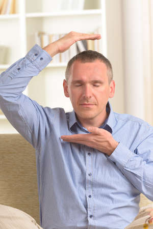 transfering: Man practicing self Reiki transfering energy through palms, meditating.