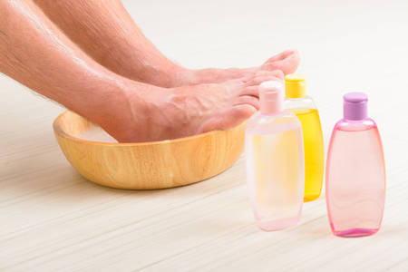 feet washing: Male feet in a bowl with water and soap, cosmetics in bottles, hygiene and spa concept