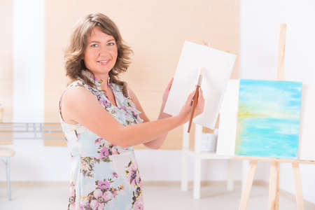 Beautiful woman painting on canvas at her home or workshop photo