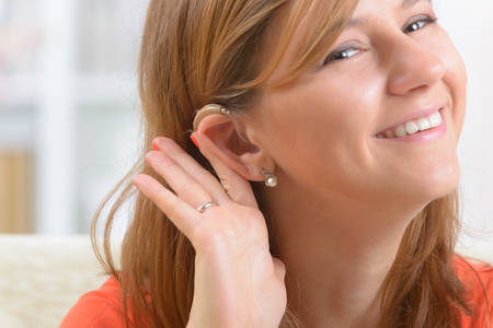 Hearing: Young, smiling woman wearing deaf aid Stock Photo