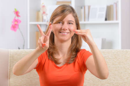 deaf: Beautiful smiling deaf woman using sign language showing V and E letters as a part of love word