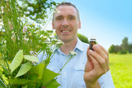 homeopath: Man homeopath herbalist picking up wild herbs with a bottle in hand