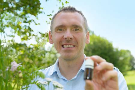 herbolaria: Hombre home�pata herbolario recoger hierbas silvestres con una botella en la mano Foto de archivo