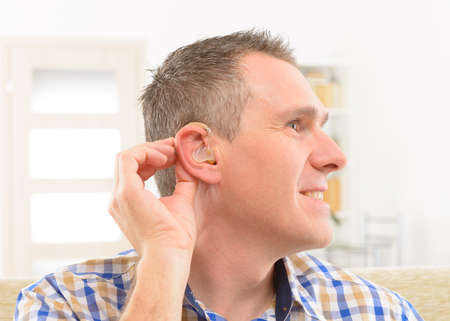 deafness: Man showing deaf aid in ear Stock Photo