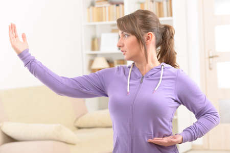 martial art: Beautiful woman doing qi gong tai chi exercise at home