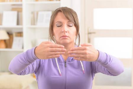 taichi: Beautiful woman doing qi gong tai chi exercise at home