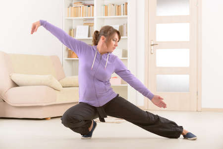Beautiful woman doing qi gong tai chi exercise at home