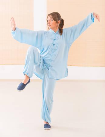 Beautiful woman doing qi gong tai chi exercise wearing professinal, oryginal chinese clothes at gym Фото со стока