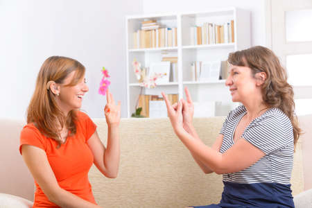 sign language: Smiling deaf woman learning sign language and talking with her teacher Stock Photo