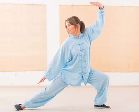 Beautiful woman doing qi gong tai chi exercise wearing professinal, oryginal chinese clothes at gym Stock Photo