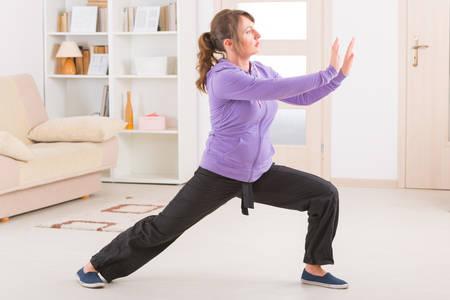 chi: Beautiful woman doing qi gong tai chi exercise at home