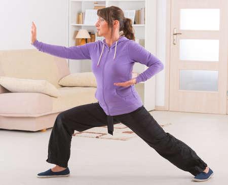 Schöne Frau macht Qi Gong Tai Chi-Übung zu Hause