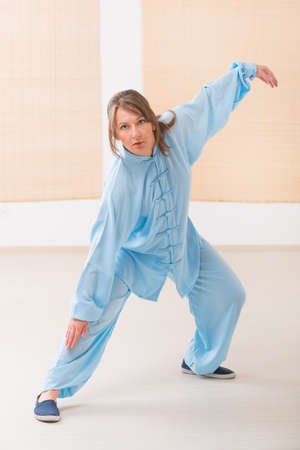 tai chi: Beautiful woman doing qi gong tai chi exercise wearing professinal, oryginal chinese clothes at gym Stock Photo
