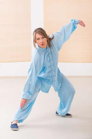 qigong: Beautiful woman doing qi gong tai chi exercise wearing professinal, oryginal chinese clothes at gym Stock Photo