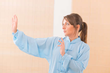 oryginal: Beautiful woman doing qi gong tai chi exercise wearing professinal, oryginal chinese clothes at gym Stock Photo