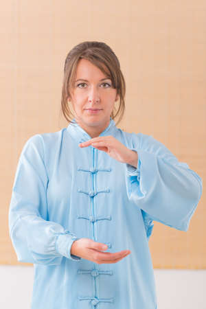 qi: Beautiful woman doing qi gong tai chi exercise wearing professinal, oryginal chinese clothes at gym Stock Photo