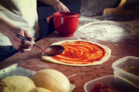 Fresh original Italian raw pizza, preparation in traditional style.