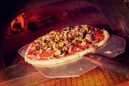 シャベルで新鮮な元イタリアのピザは伝統的な薪の石釜に入れています。
