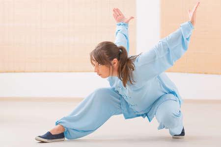 Schöne Frau macht Qi Gong Tai Chi Übung tragen professionelle, original chinesischen Kleidung an der Gymnastik Standard-Bild