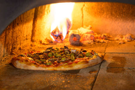 Fresh original Italian pizza in a traditional wood-fired stone oven. photo