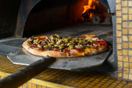 fire bricks: Fresh original Italian pizza on a shovel is putting out a traditional wood-fired stone oven. Stock Photo