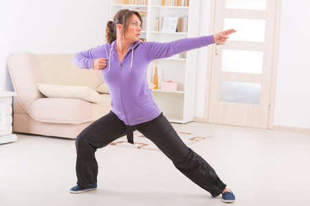 tai chi: Beautiful woman doing qi gong tai chi exercise at home