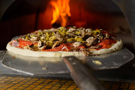 mattoncini: Fresh originale pizza italiana su una pala sta mettendo in un tradizionale pietra forno a legna.