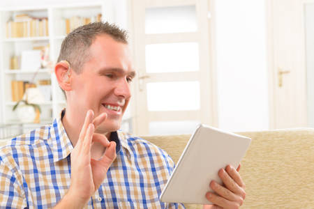 deafness: Smiling Deaf man talking using sign language on the tablets Stock Photo