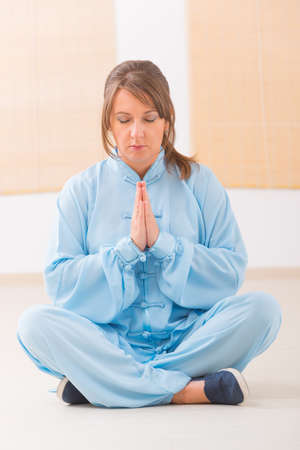 Beautiful woman meditating wearing professinal, oryginal chinese clothes at gym Stock Photo