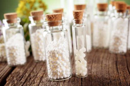Homeopathische lactose suiker bolletjes in glazen flessen Stockfoto