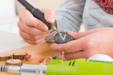 graver: Woman using a high speed rotary multi tool to engrave ornament on the stone