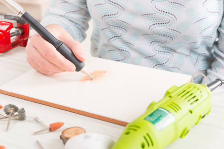 engraver: Woman using a high speed rotary multi tool to engrave ornament on the tile Stock Photo